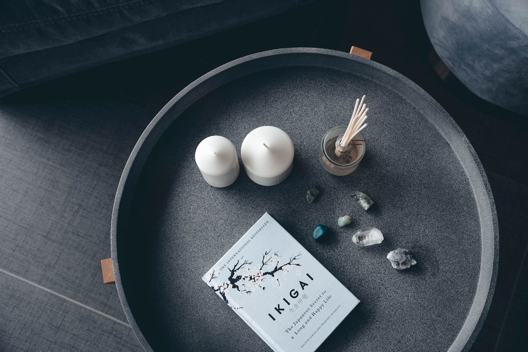 White candles and a book about happy life are neatly arranged on a gray table / tray.