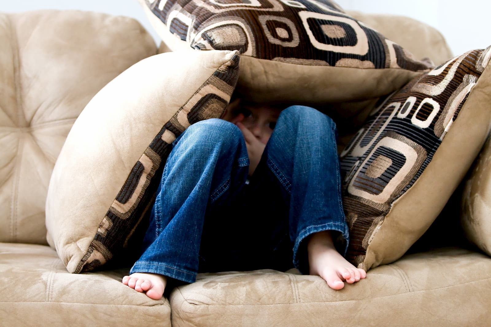 A boy peeks out from his hiding place made of cushions