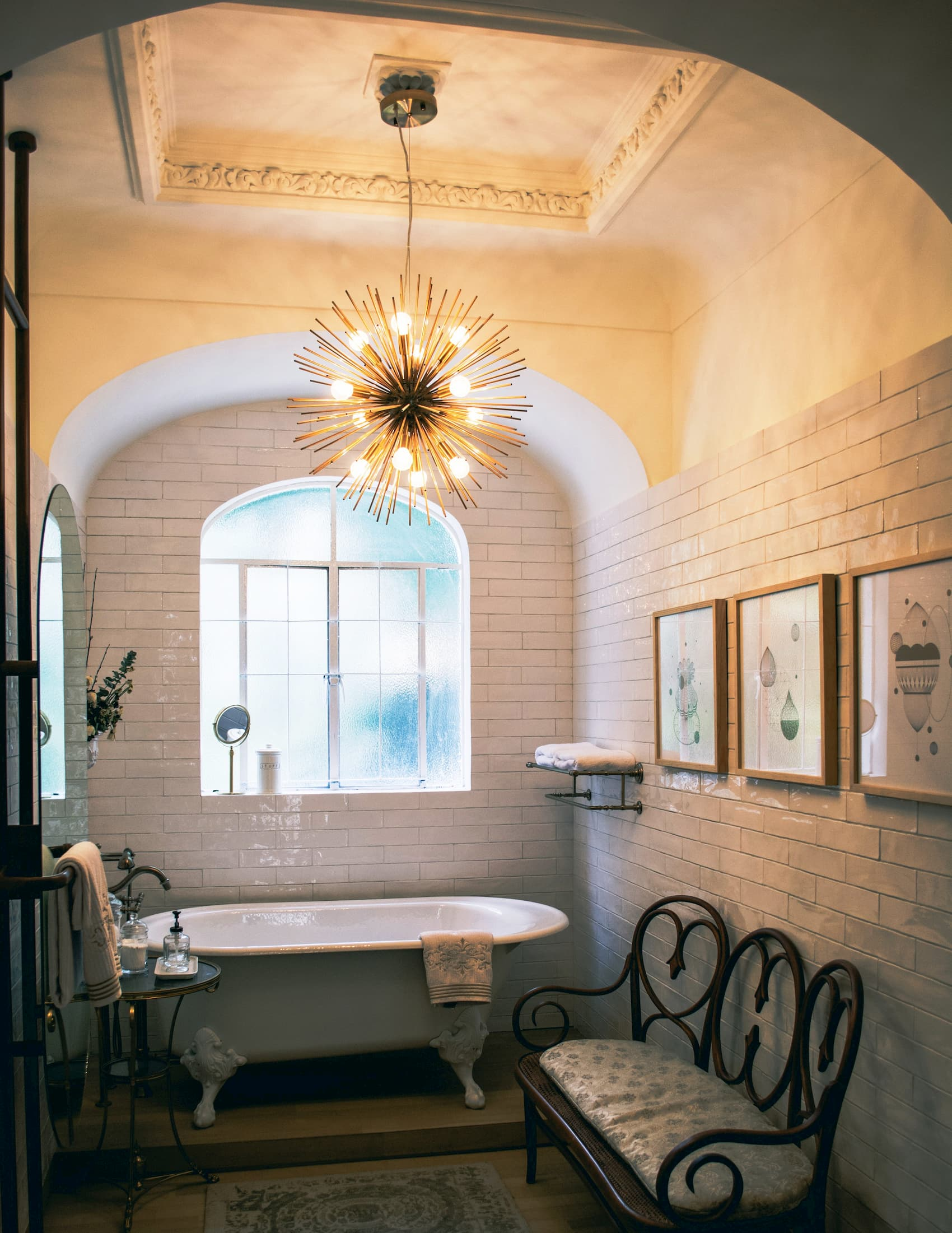 A square bathroom with cornice, a rug, a sofa, pictures, a chandelier hanging from the ceiling, and an antique tub standing on legs