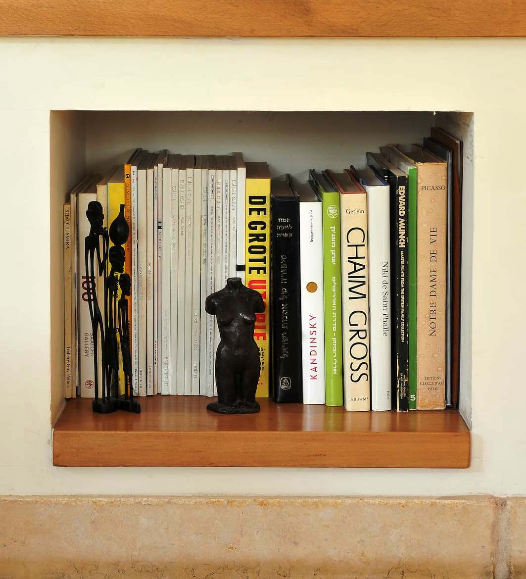 Books in a square niche built into a wall with a wooden shelf base