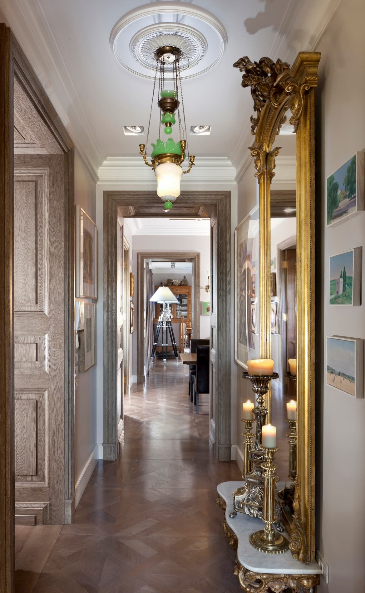 A corridor divided into sections by wooden door frames with a light oak floor and cornices framing the ceiling. A gilded mirror hangs on the wall with 3 antique bronze candlesticks beside it.