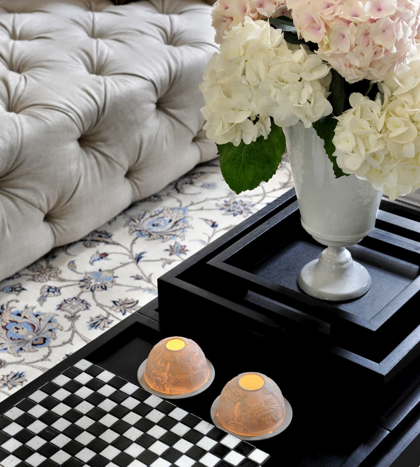 White velvet capitonnage sofa on Chinese silk carpet of light gray and white next to a dark brown wooden table with a white flower vase.