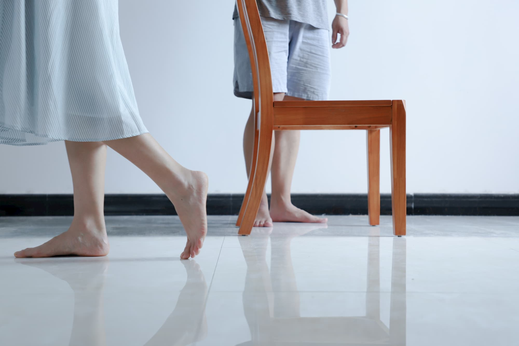 Two people and a chair standing on a smooth, reflective floor