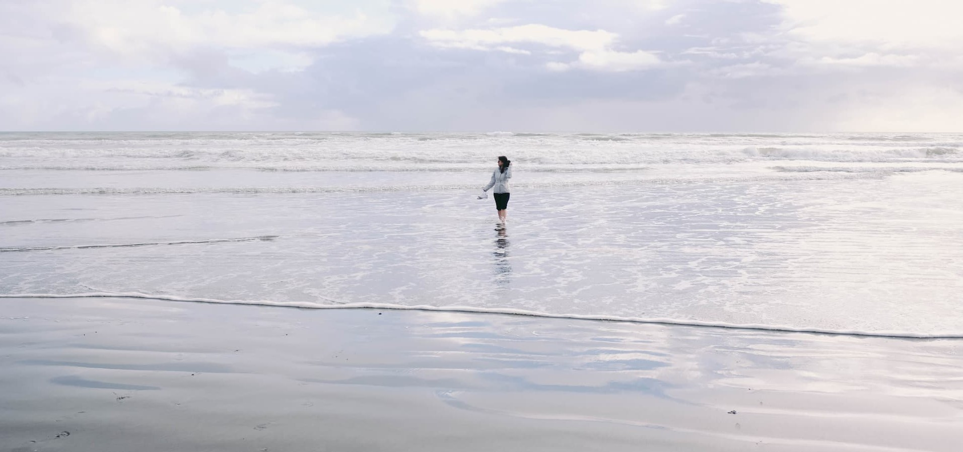 A girl stands in a wide, quiet sea