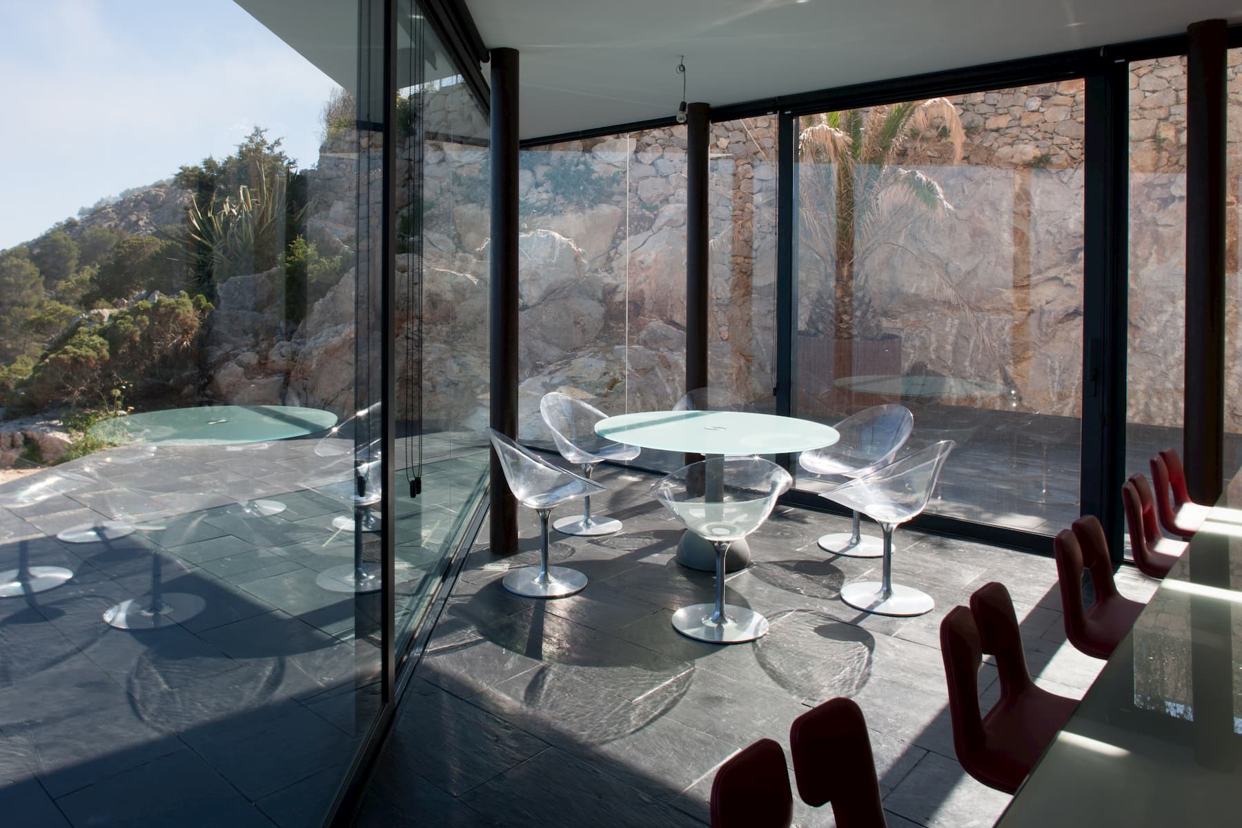 A dining room with gray tile floor, glass walls, and transparent chairs looks over a patio with a stone wall behind it