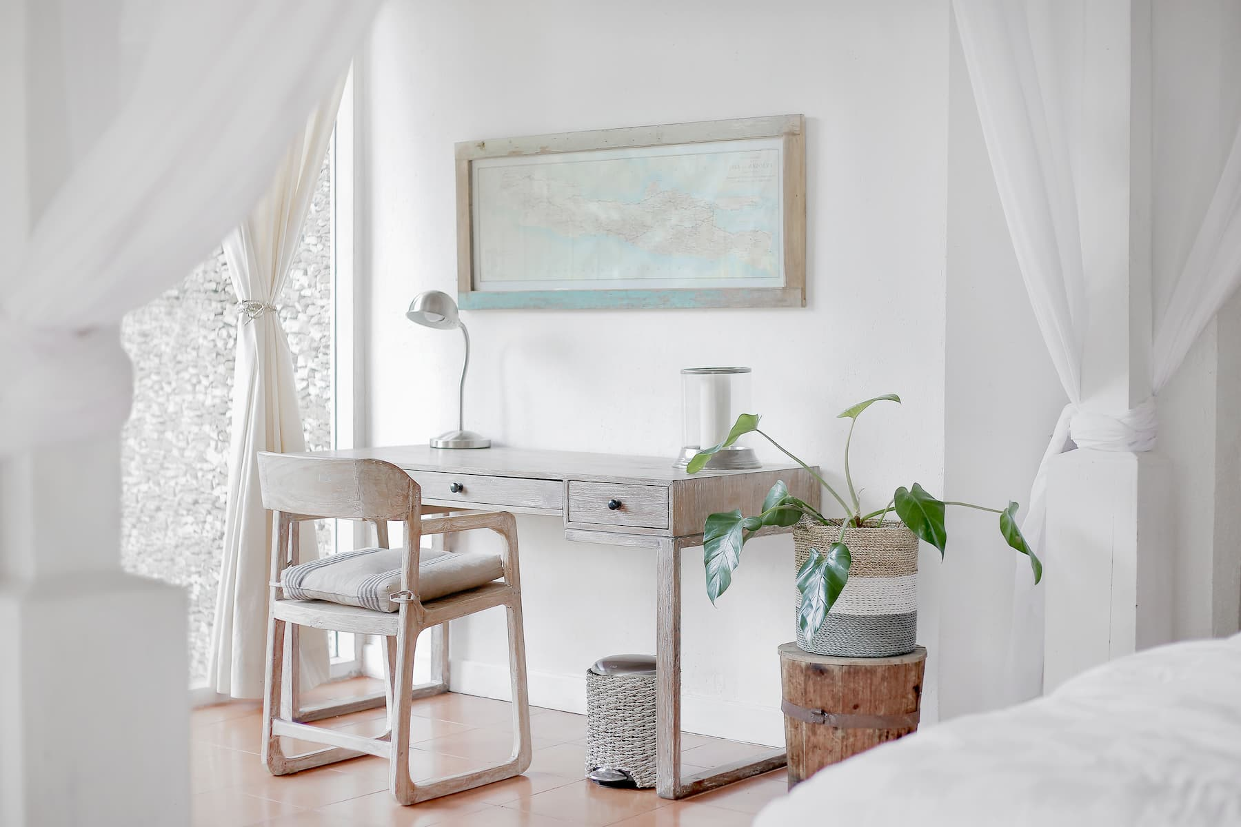 Brightly-lit white room, white handmade wooden desk and chair and white curtains