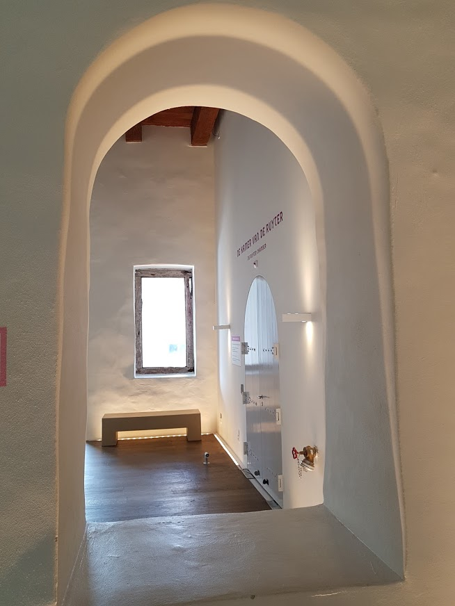 Through an arched window, a room with coarse plaster, wooden beams, and wood floor.