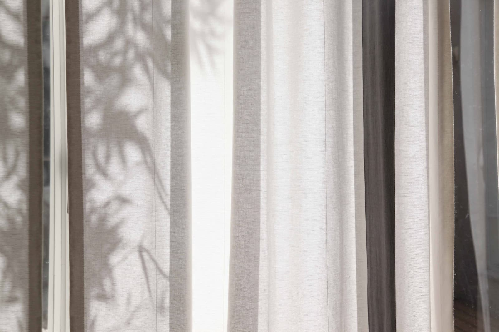 A linen curtain that displaying silhouettes of the tree leaves outside behind it