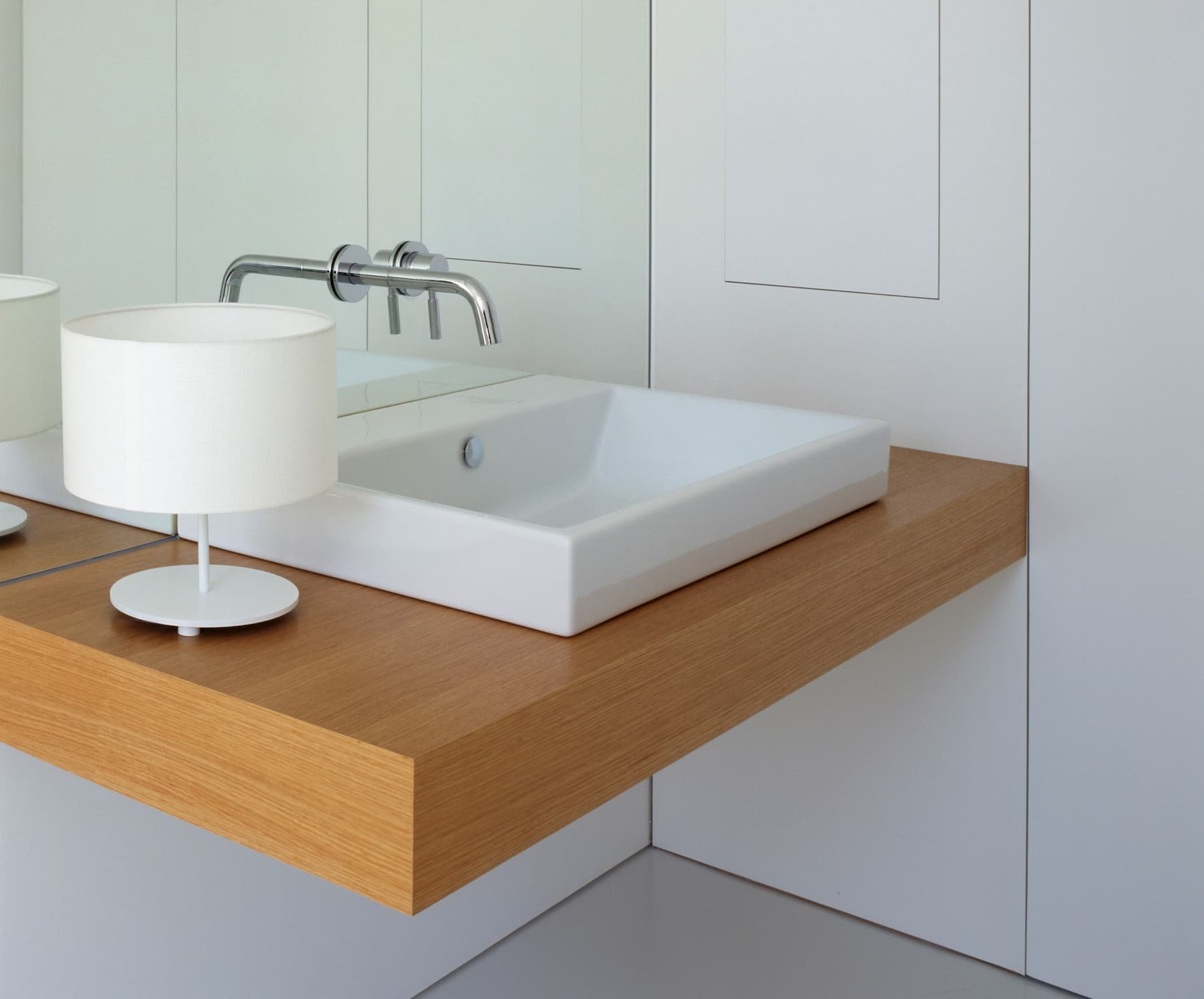 A narrow, rectangular white sink on a floating oak shel