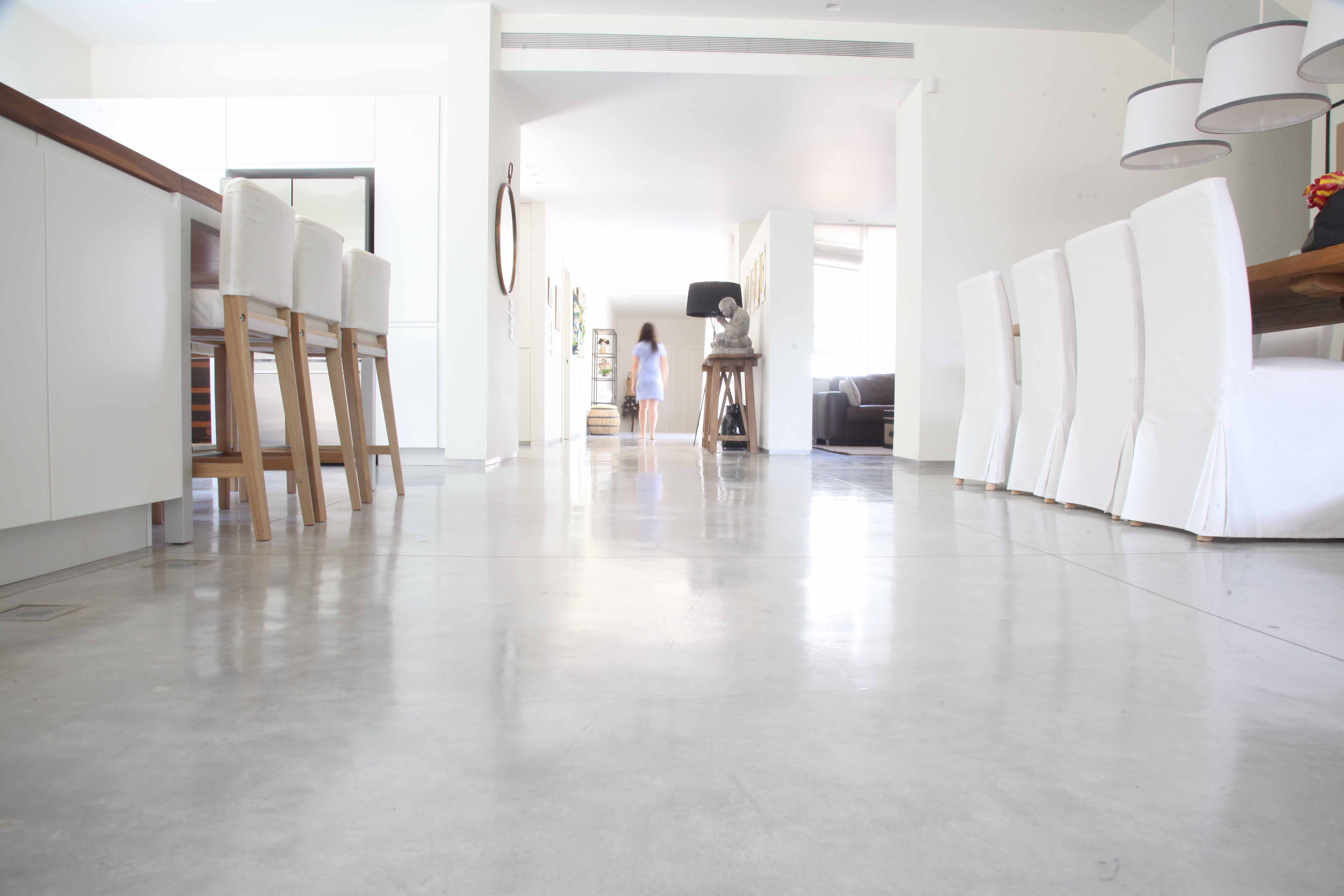 Open space in a house with a smooth concrete floor. Furniture in white and light gray