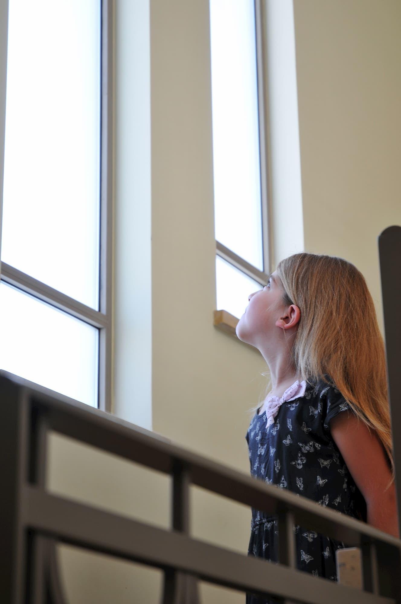 Girl looking up at elongated windows
