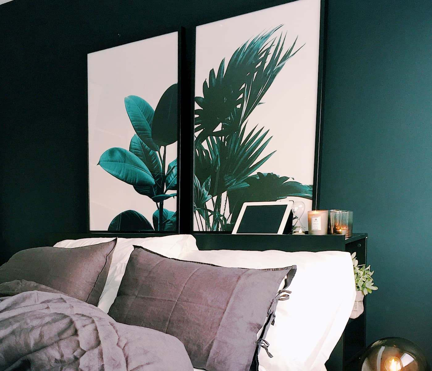 On a dark green wall on behind the backboard of a bed are two pictures showing large, green leaves on a white background