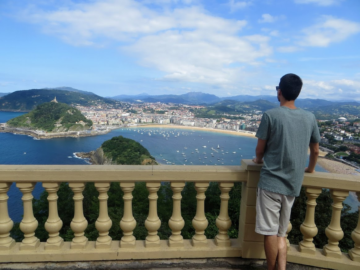 A man stands on a balcony overlooking the landscape spread out before him