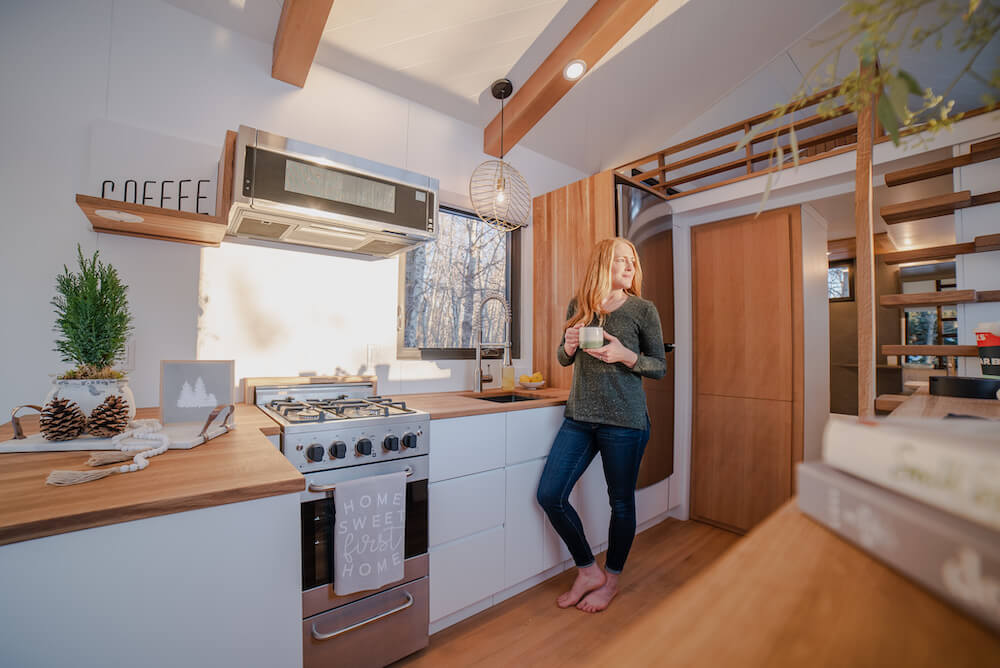 Woman standing in beautiful modern tiny house kitchen