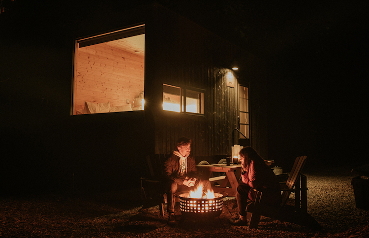 Couple enjoying a camp fire near a Getaway tiny house