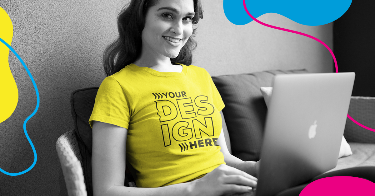 Young woman smiling to the camera, with a laptop on her lap.