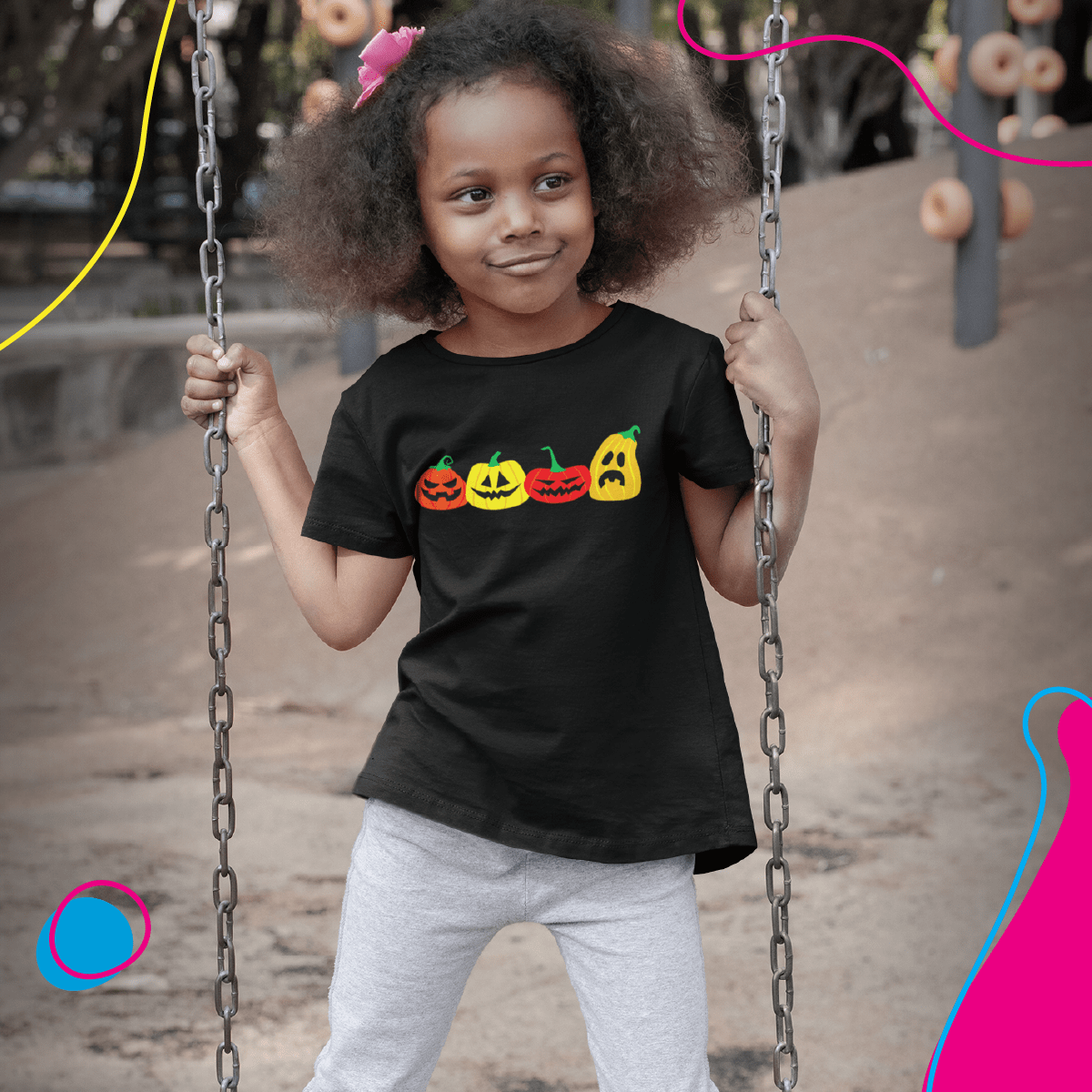 Black girl playing on a swing, wearing a POD shirt with a Halloween design on it