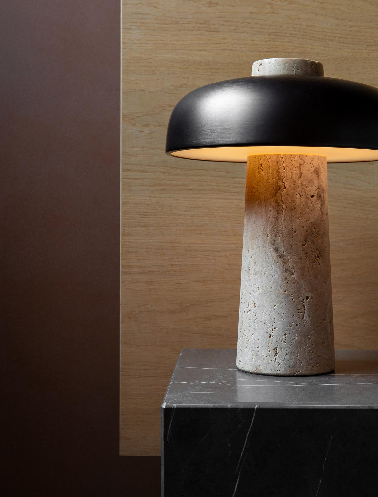 Reverse table lamp on marble plinth against oak headboard