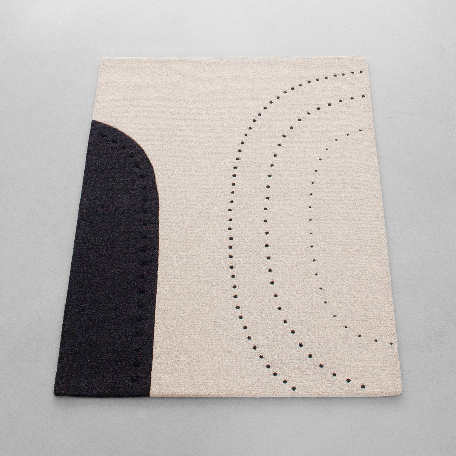 Dotted balance rug in cream and black on grey floor