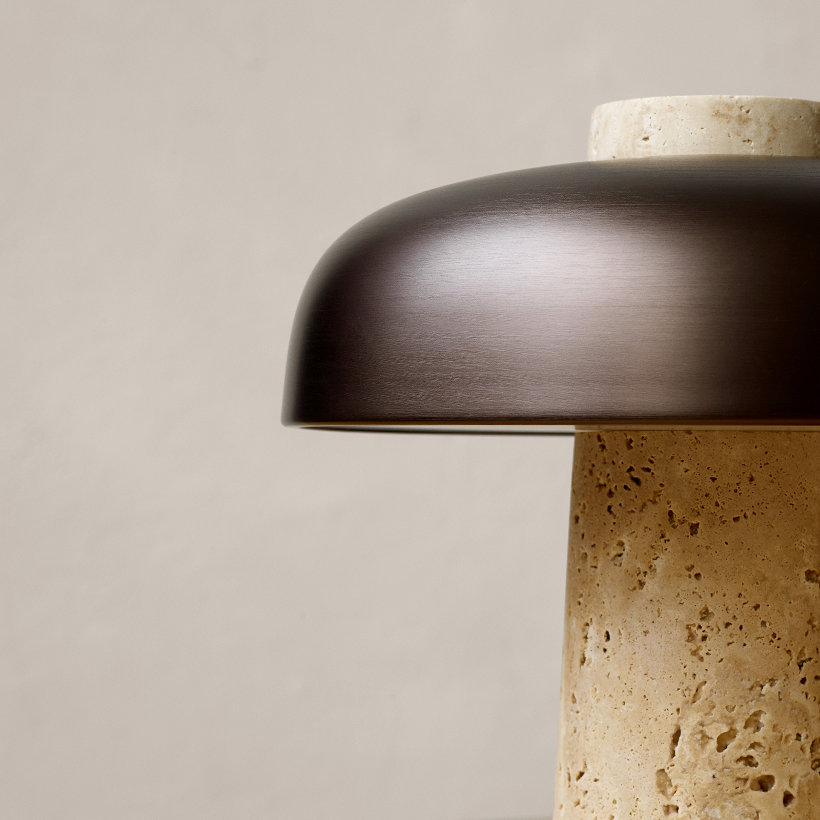 Detail of reverse table lamp in travertine and bronze