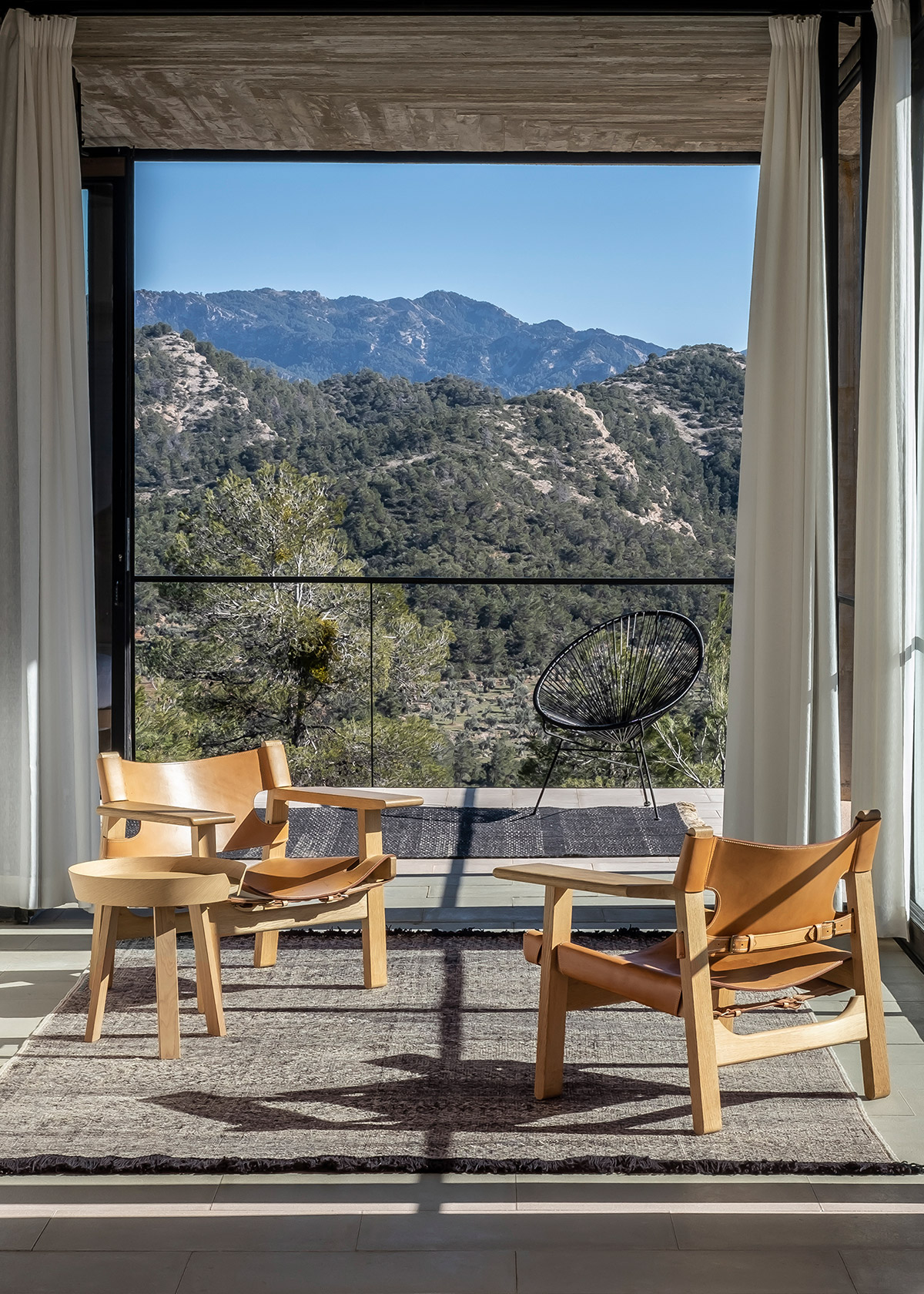 Telares rug and Spanish chair in modern concrete room with view of mountains