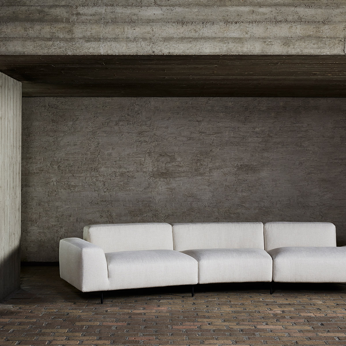 Endless sofa by Bensen in cream fabric against a concrete wall