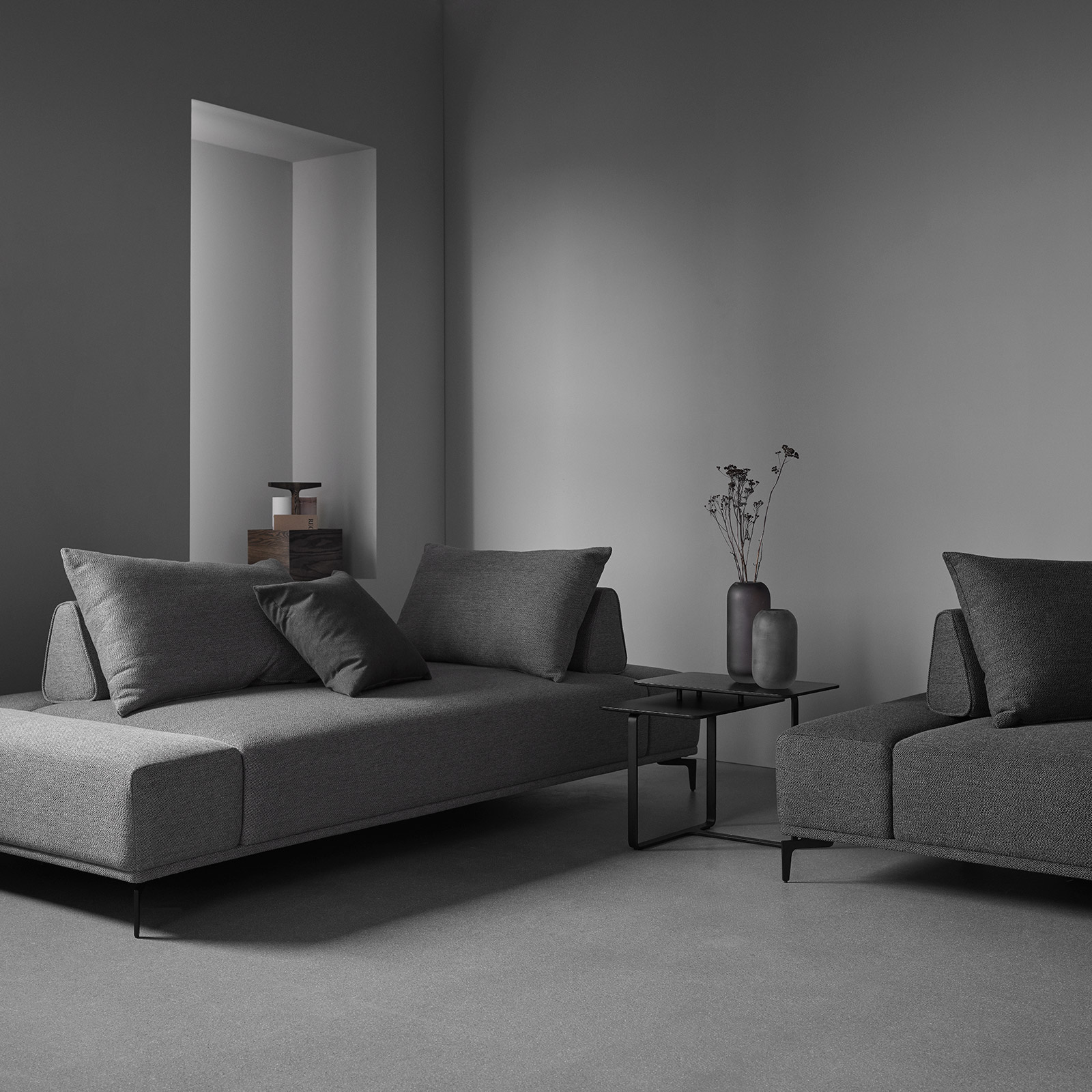 Define sofa by Wendelbo in dark grey fabric in grey minimal room