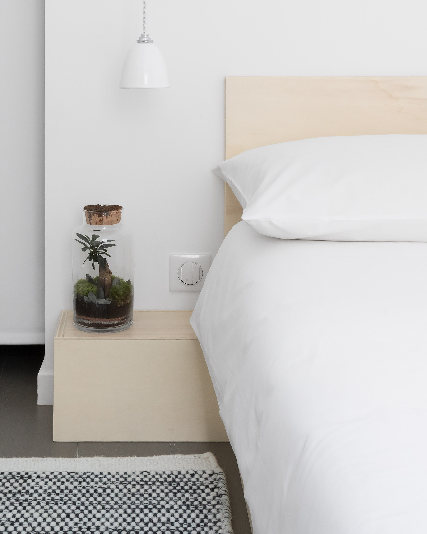 Minimal Japanese plywood bed, white linen, bedside table with bonsai terrarium, black and white rug