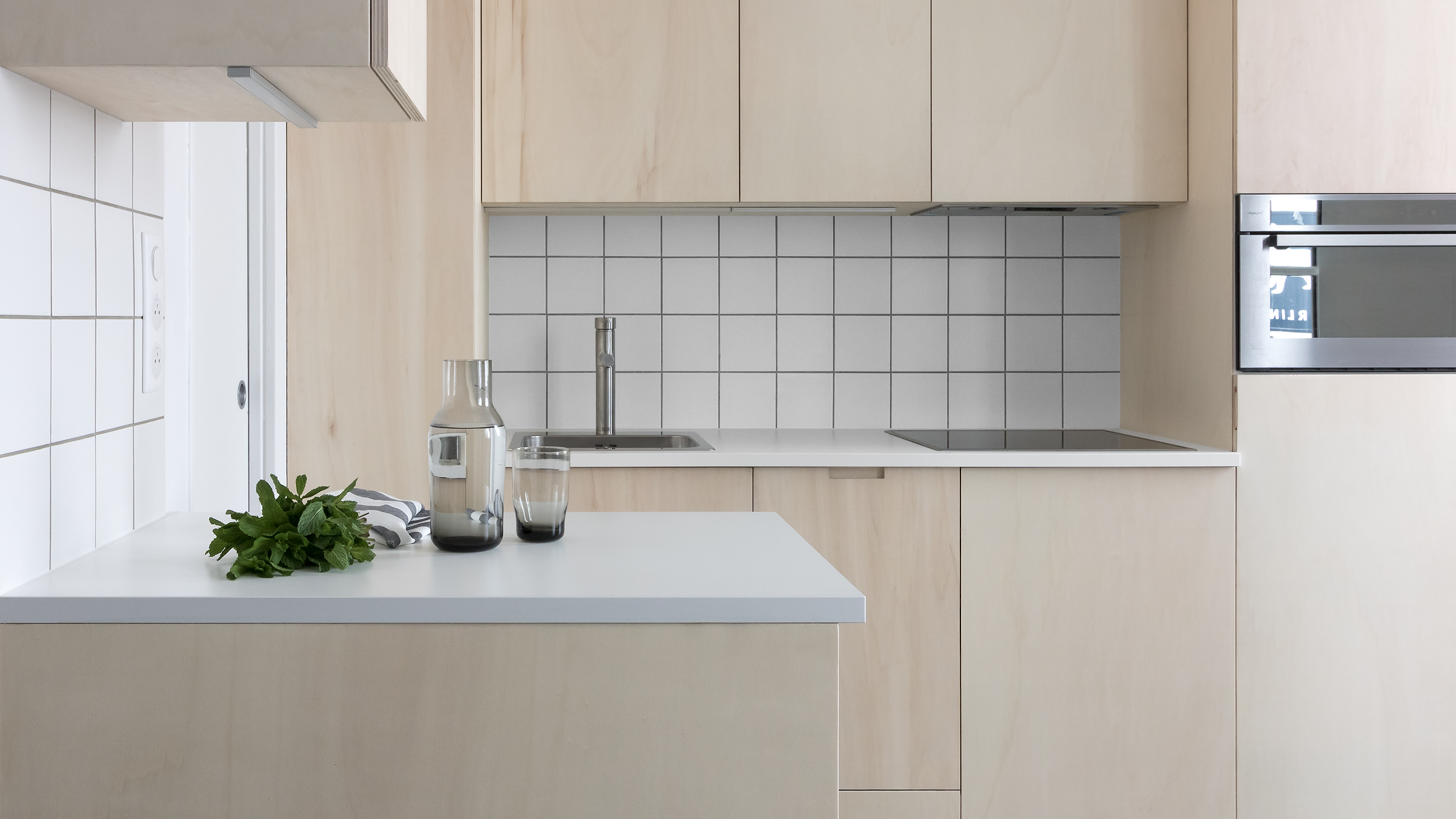 Modern minimal Japanese plywood kitchen with white worktop and wall tiles