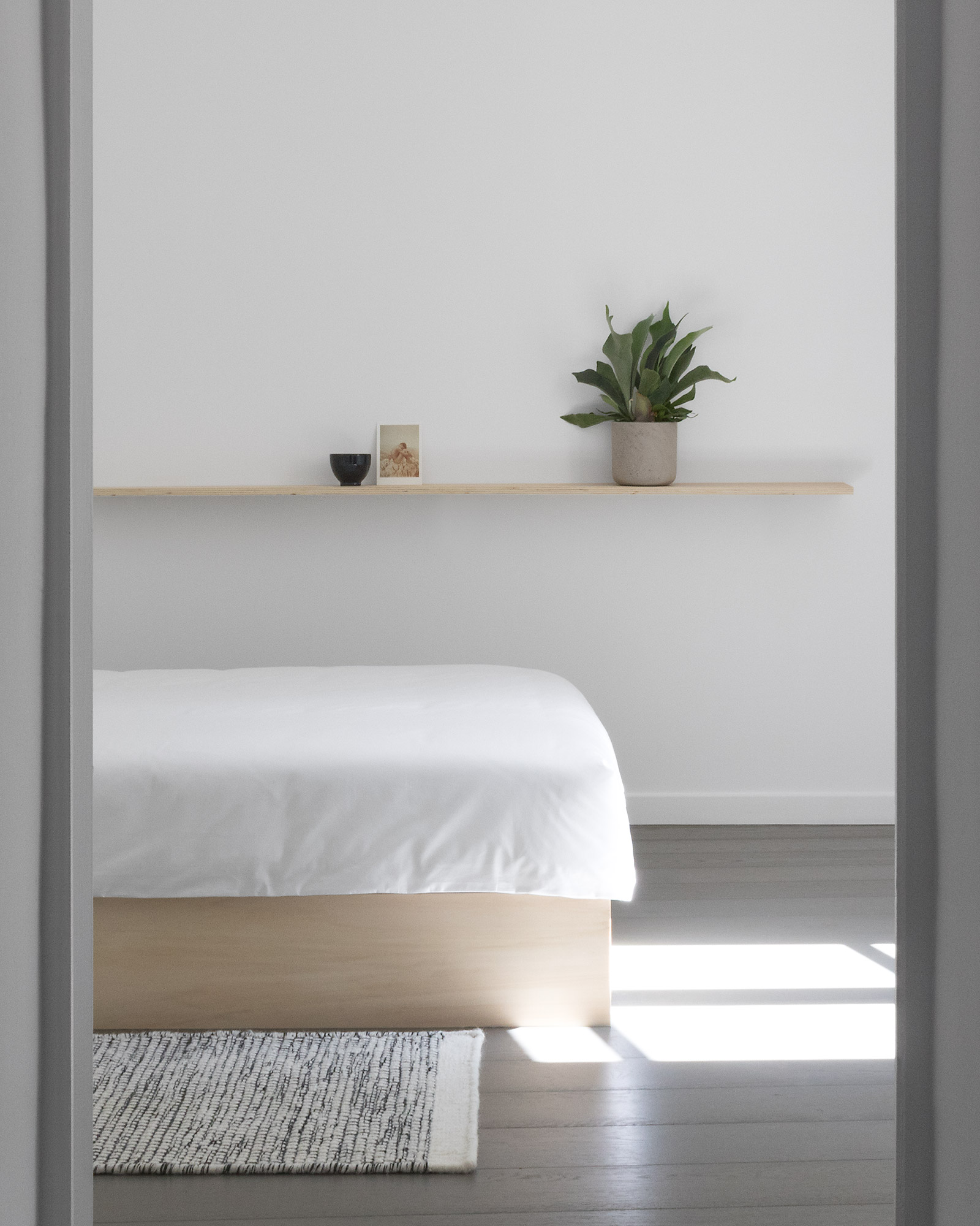 Doorway into minimal, modern Japanese style white bedroom with plywood bed