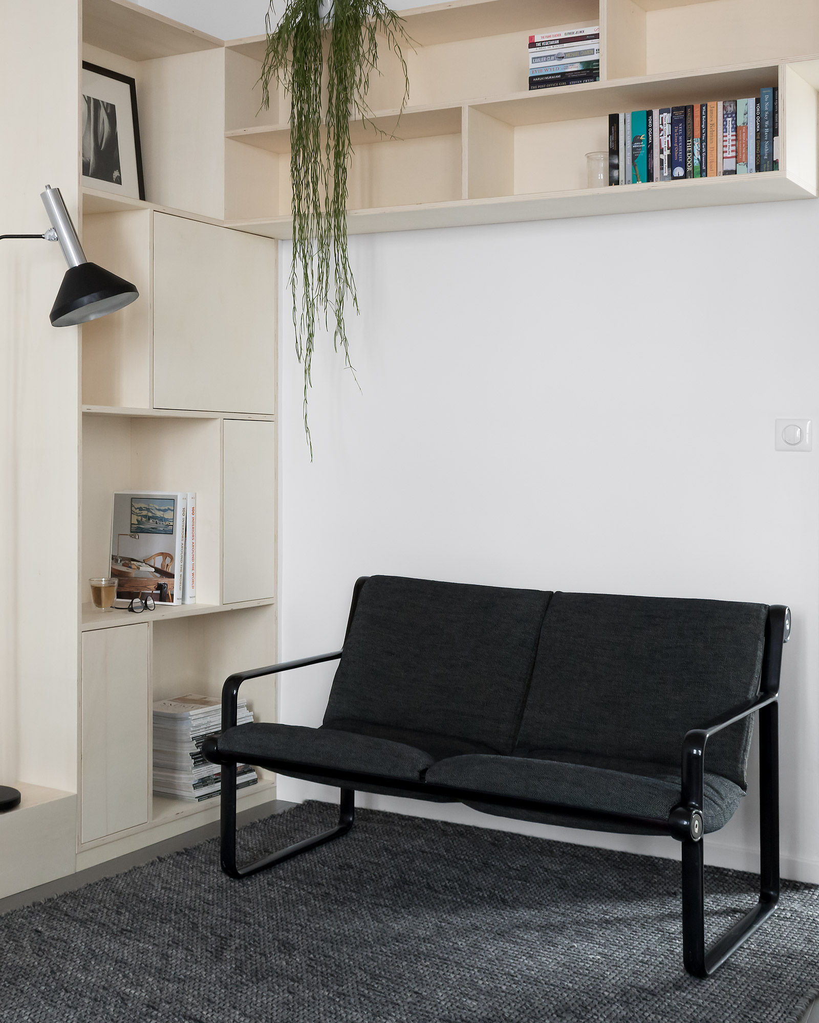 Modern Japanese style, white living room with plywood corner bookcase and dark grey 1970's Knoll sofa