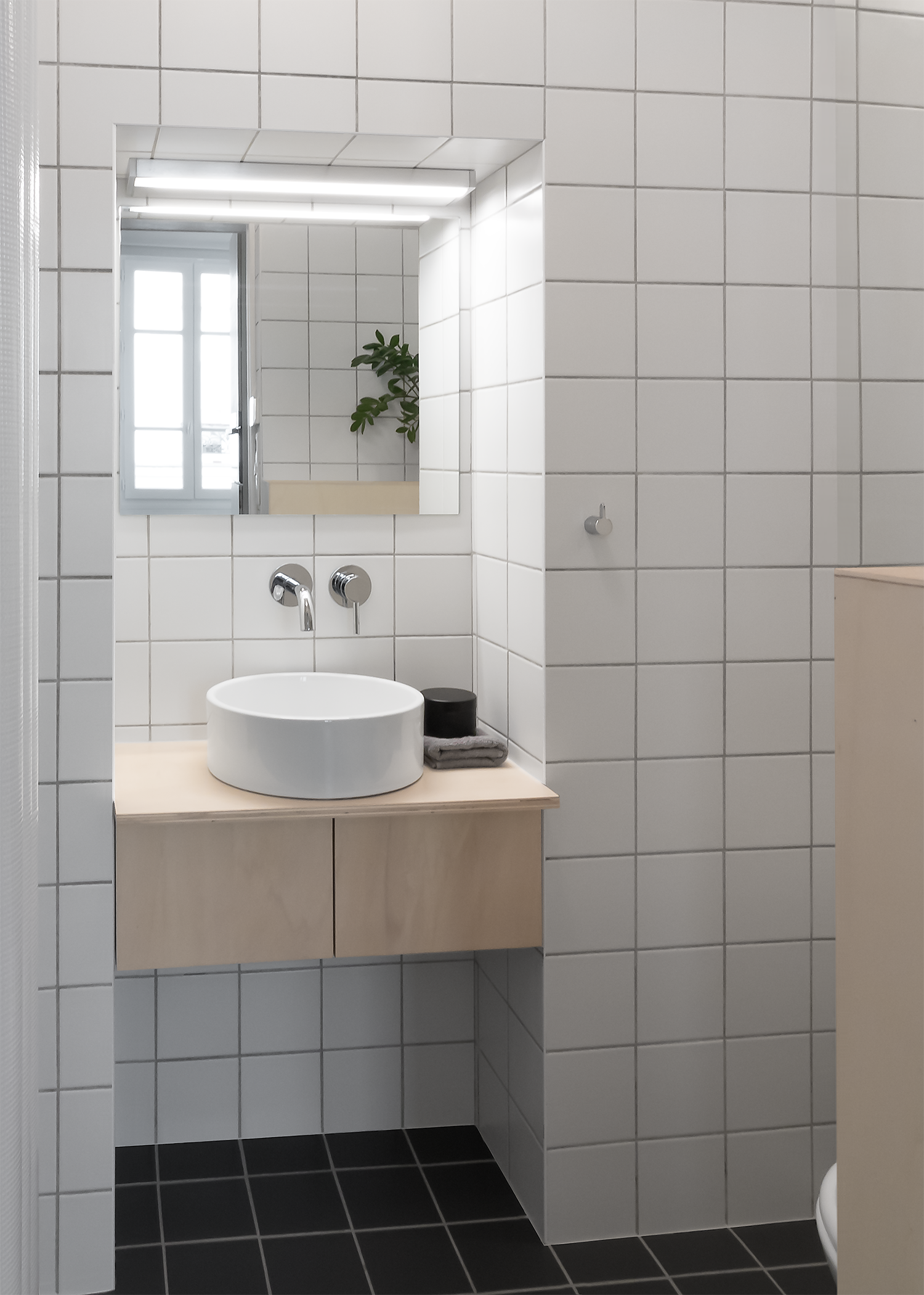 Japanese style minimal bathroom with square white wall and grey floor tiles and plywood cabinet