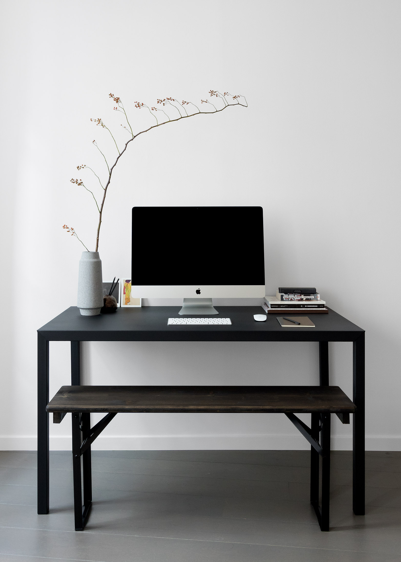 Japanese style home study. Black metal desk with iMAC and ikebana branch