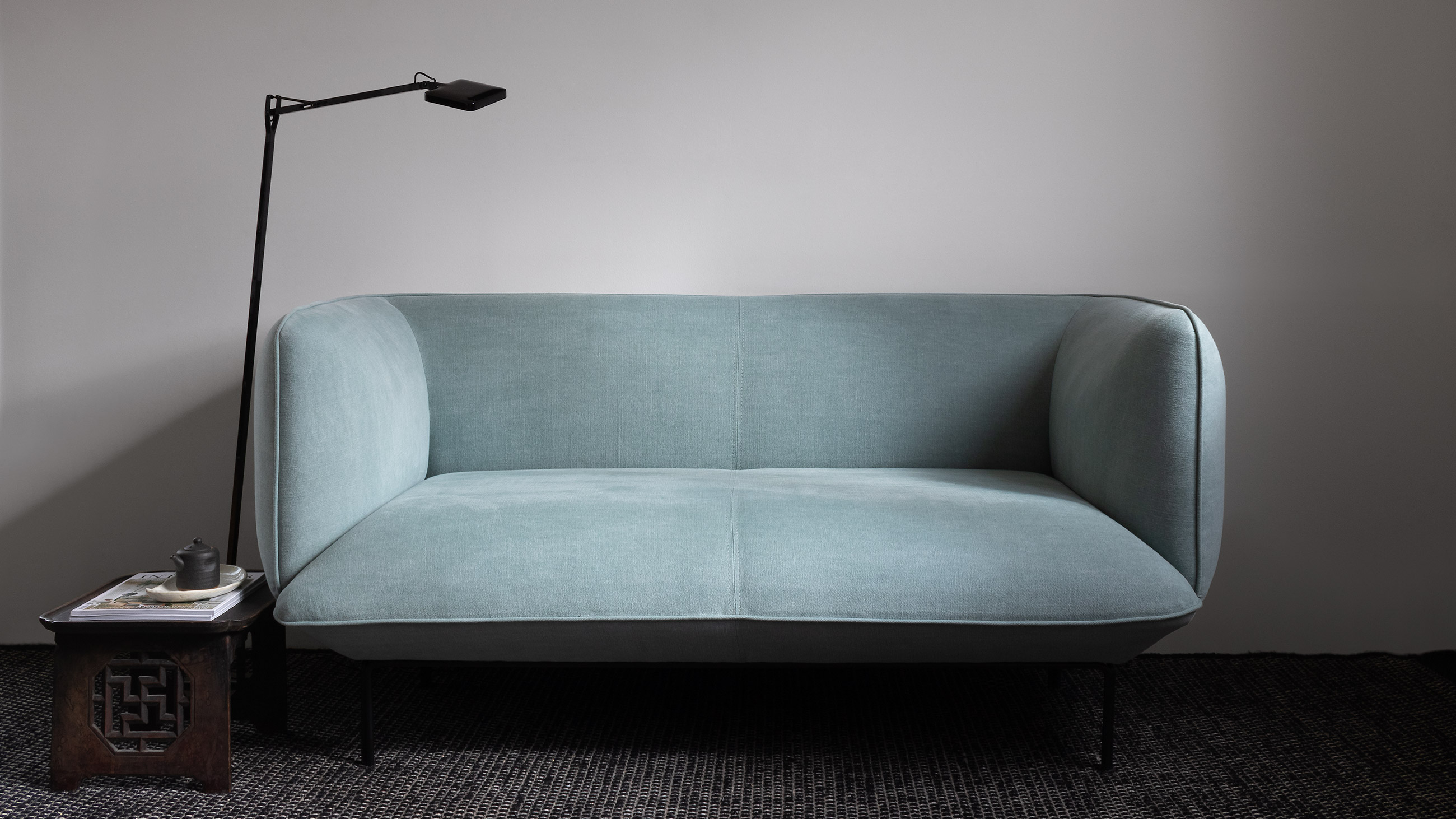 Teal Scandinavian sofa, modern black floor lamp and traditional Japanese tea table on black rug