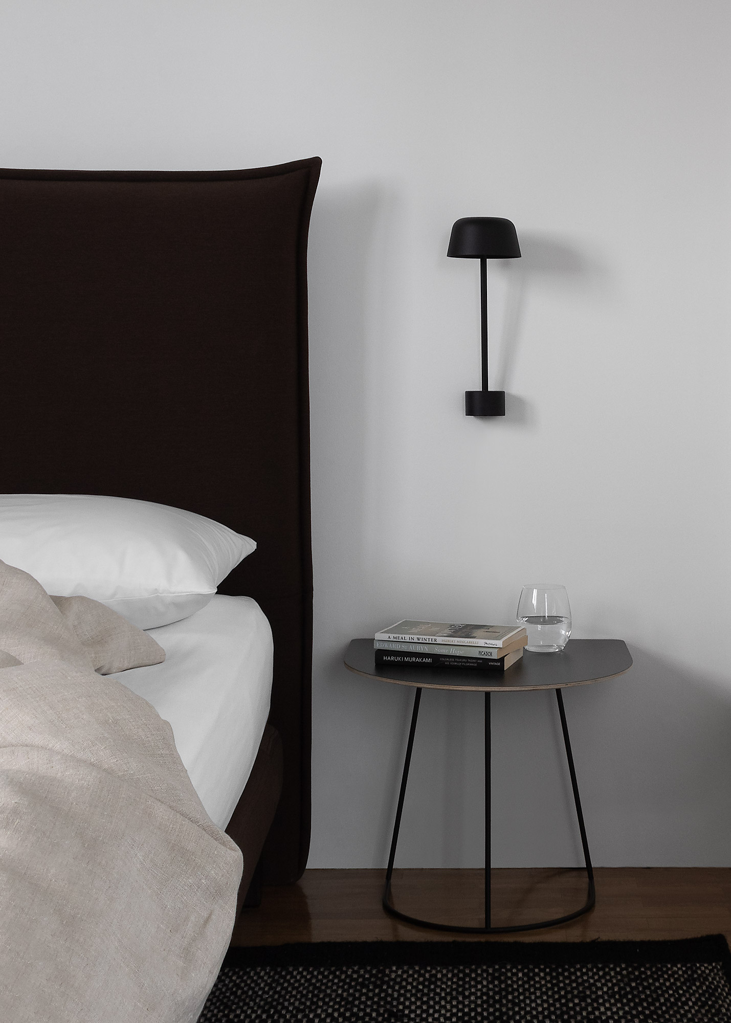 Bed with natural linen and contemporary dark wool headboard, modern black Scandinavian wall light and table, black rug