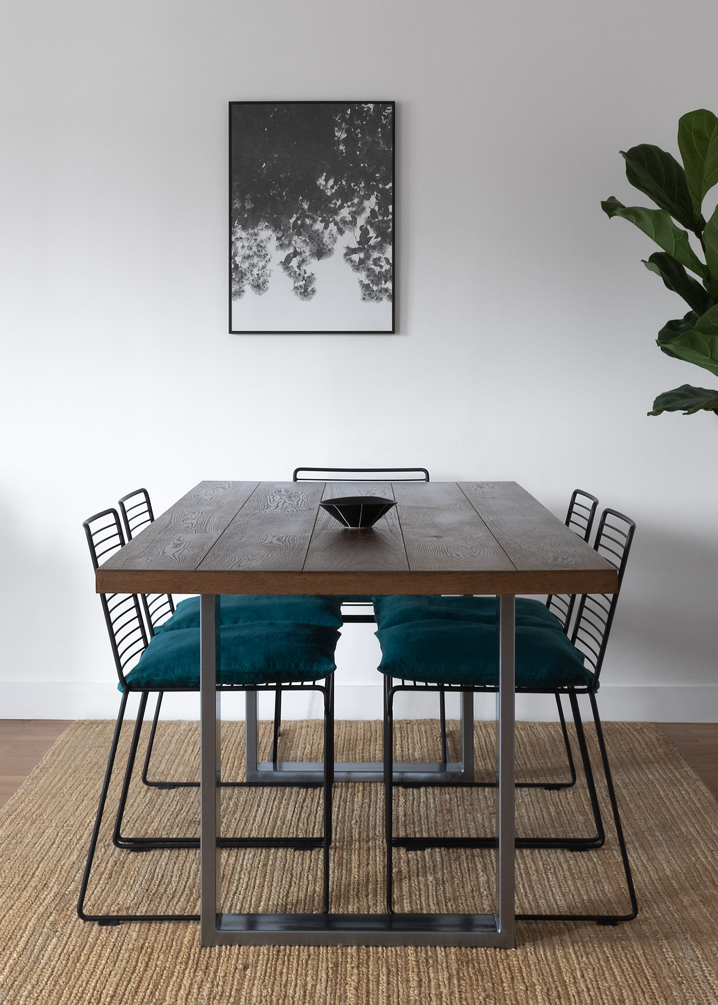 Modern oak dining table with black metal chairs and teal cushions on a jute rug