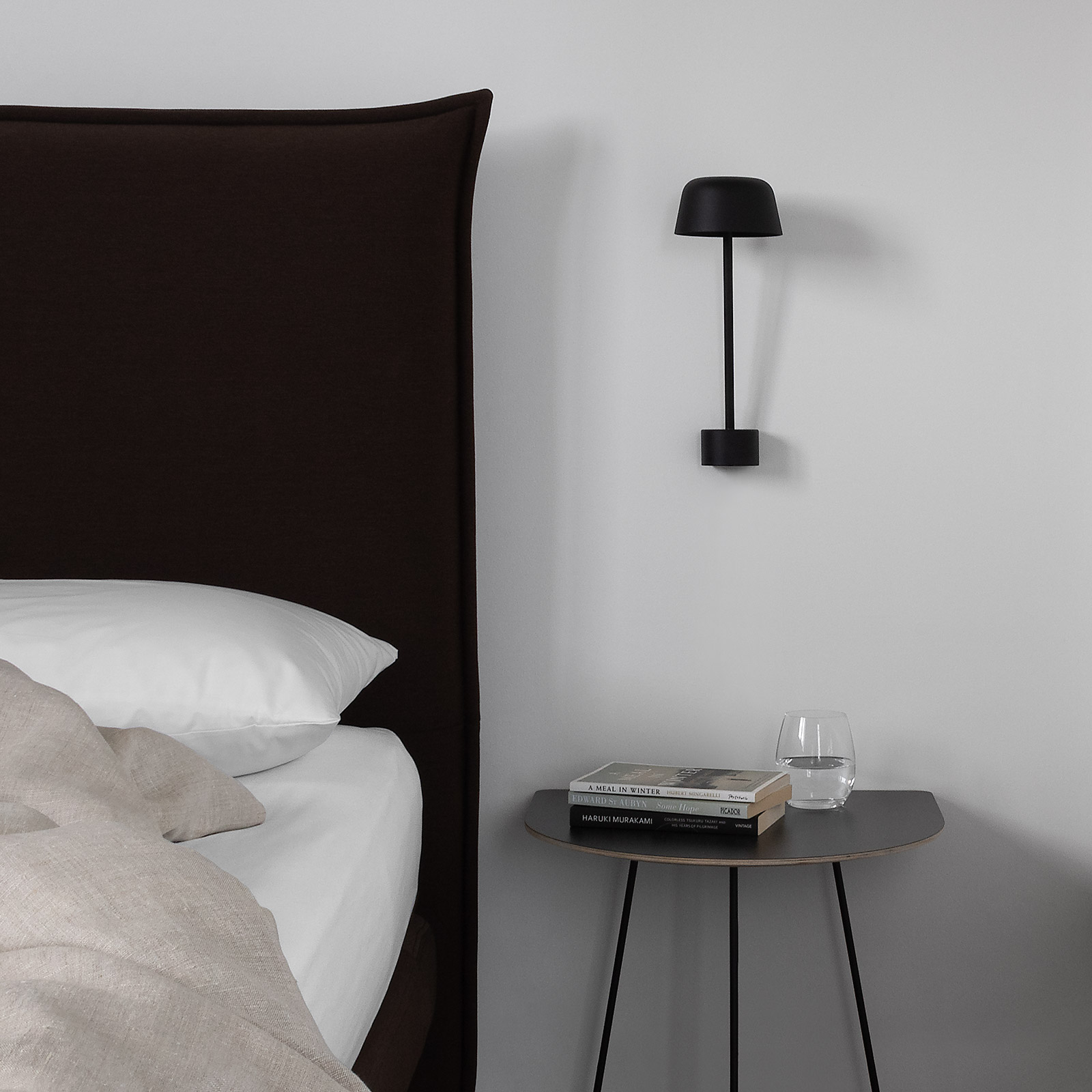 Bed with natural linen and contemporary dark brown headboard, modern black Scandinavian wall light and table