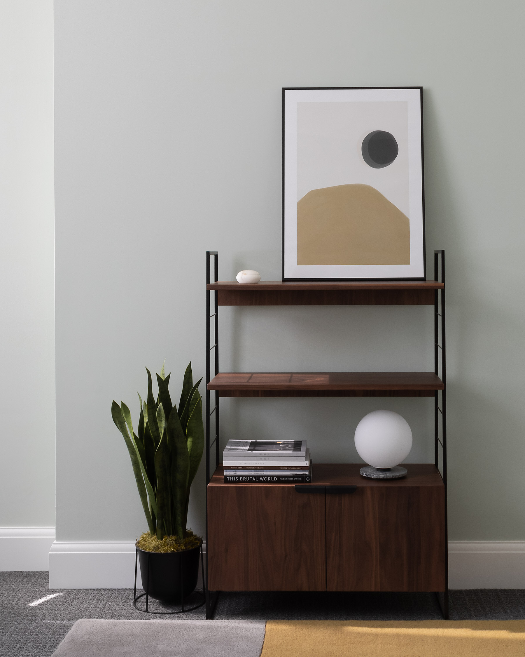 Interior with mid-century walnut cabinet, sansevieria plant, abstract art and geometric rug