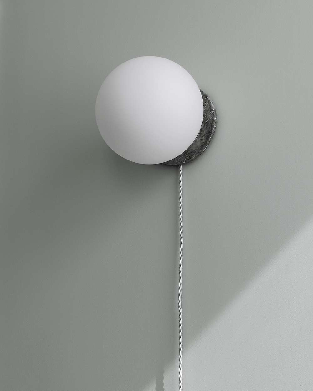 White globe wall light, grey marble base, fabric cord, grey wall