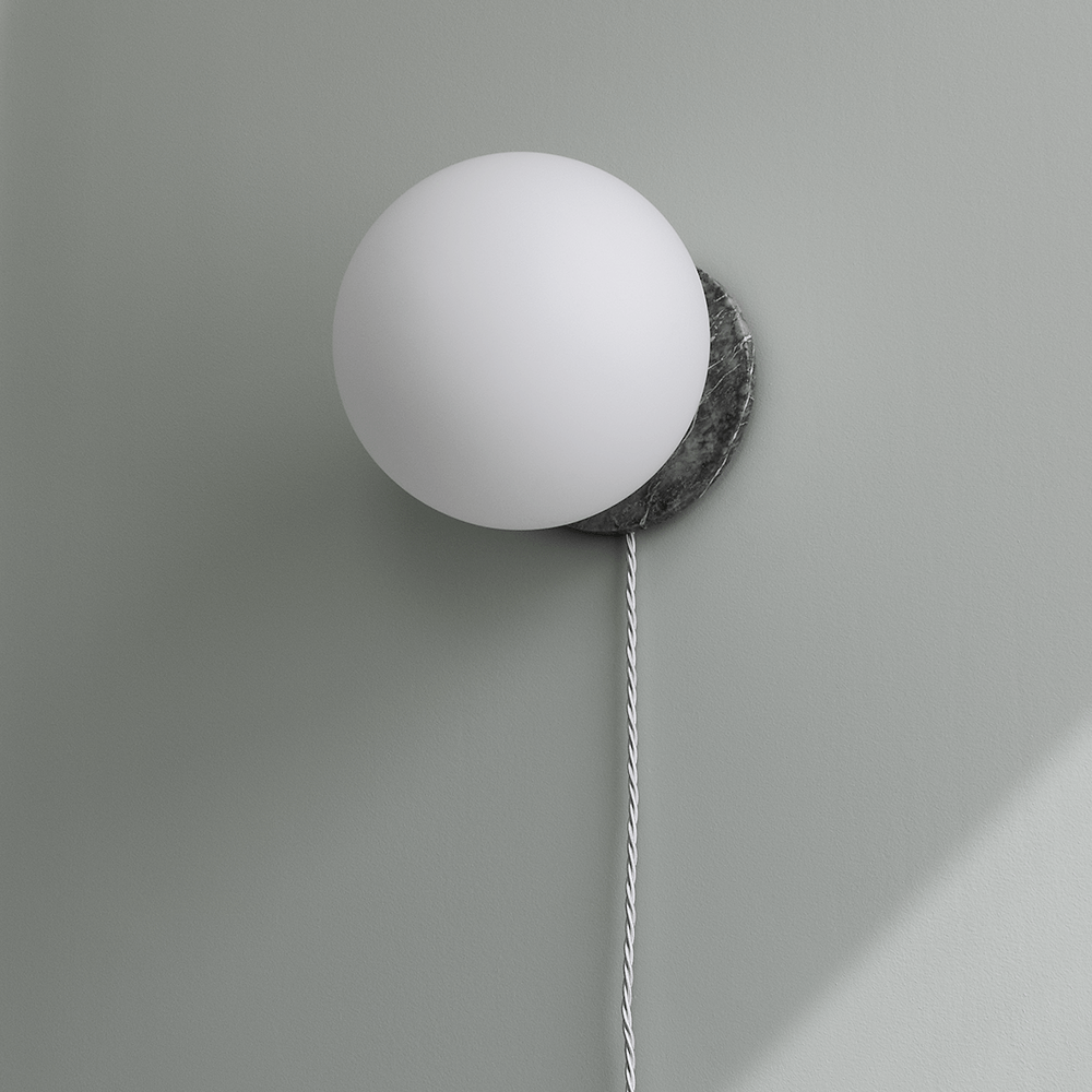 White globe wall light, grey marble base, fabric cord, grey wall