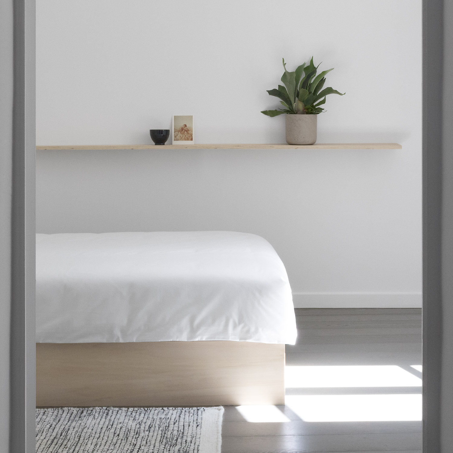 Modern minimal Japanese white bedroom with plywood bed and side table