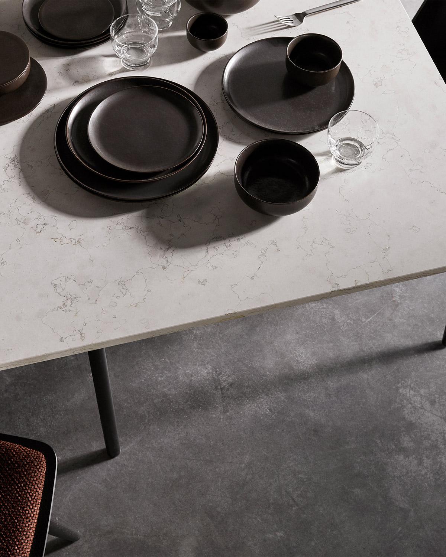Dark glazed plates on marble table, concrete floor