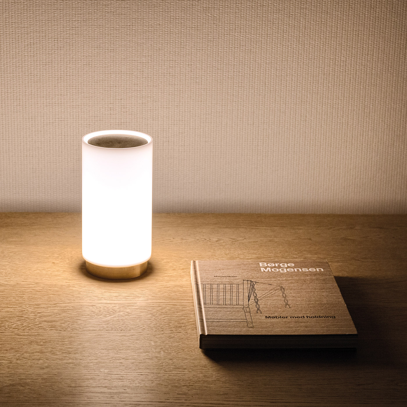 Bugia table lamp on wooden sideboard with mid-century furniture book