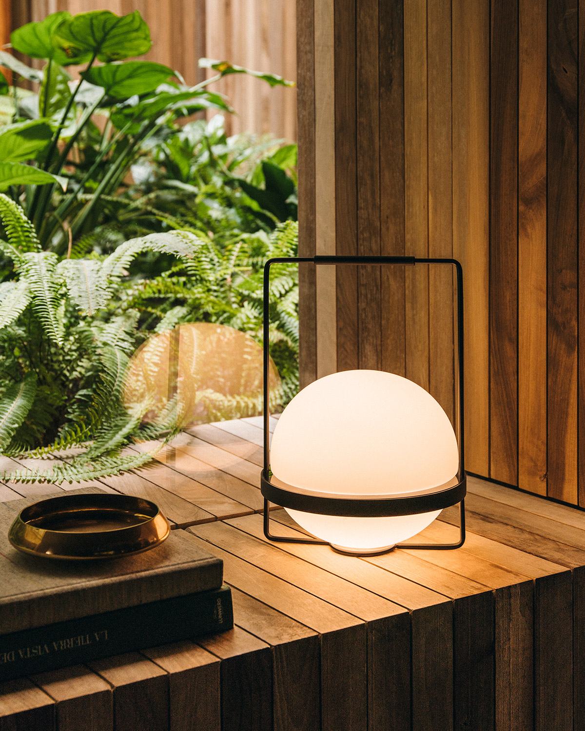 Palma table lamp by Vibia on modern wooden windowsill, background tropical plants