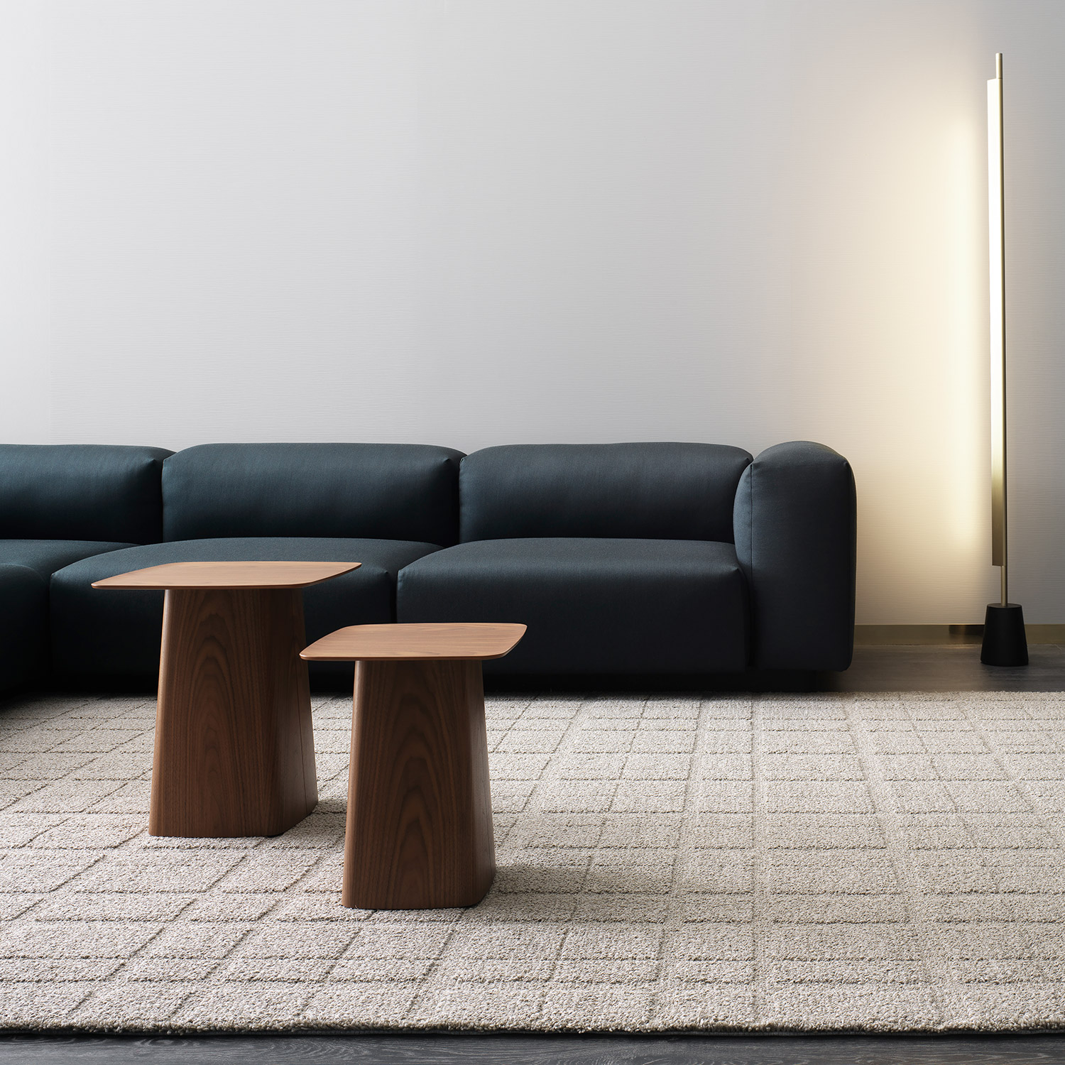 neutral wool rug, low navy sofa and modern wooden coffee tables