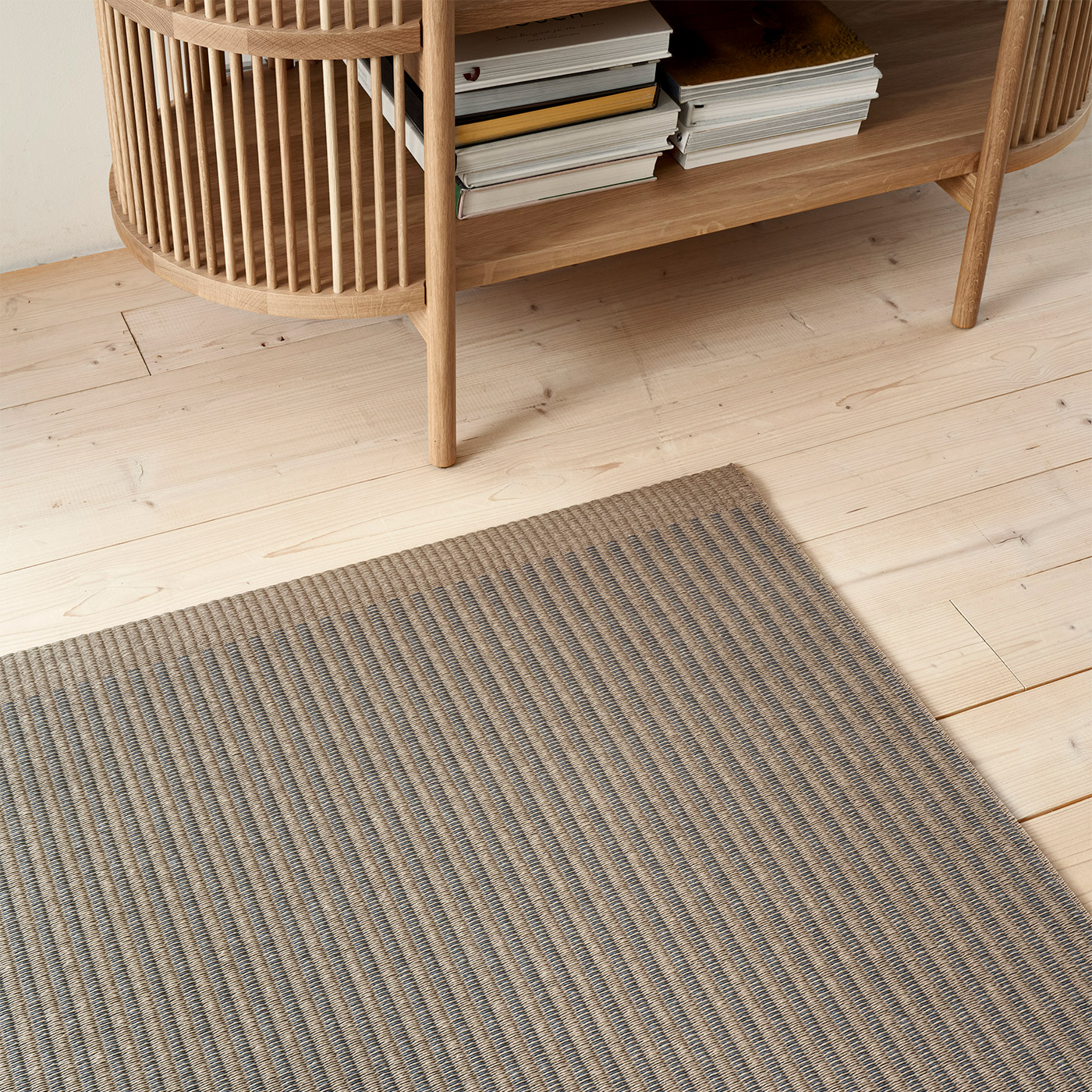 brown and grey paper yarn rug with Scandinavian wooden cupboard
