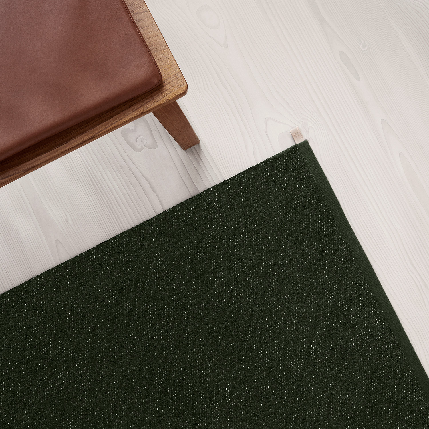 dark green chenille rug and brown leather wooden bench