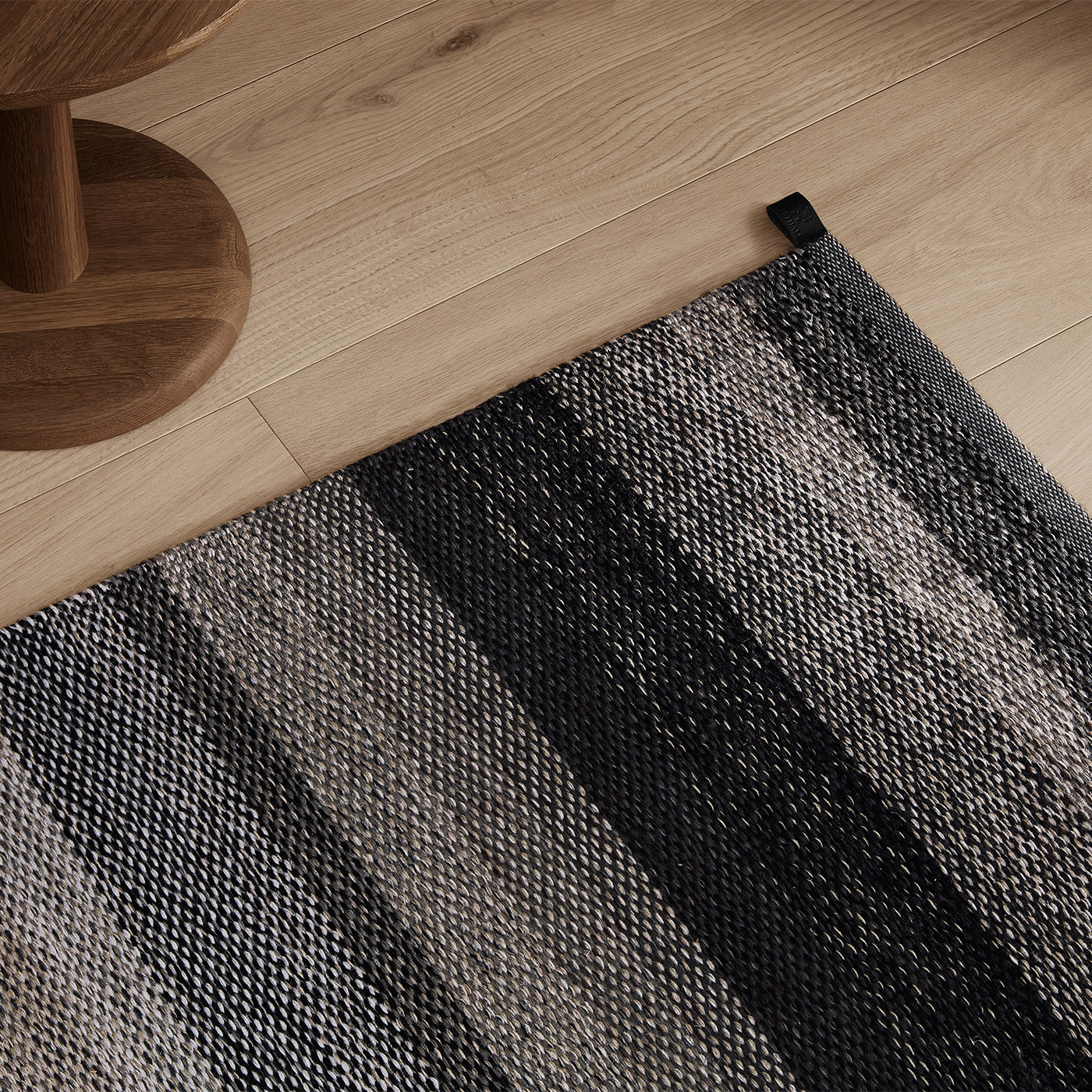 black and grey flat woven rug with light oak floor and modern smoked oak side table