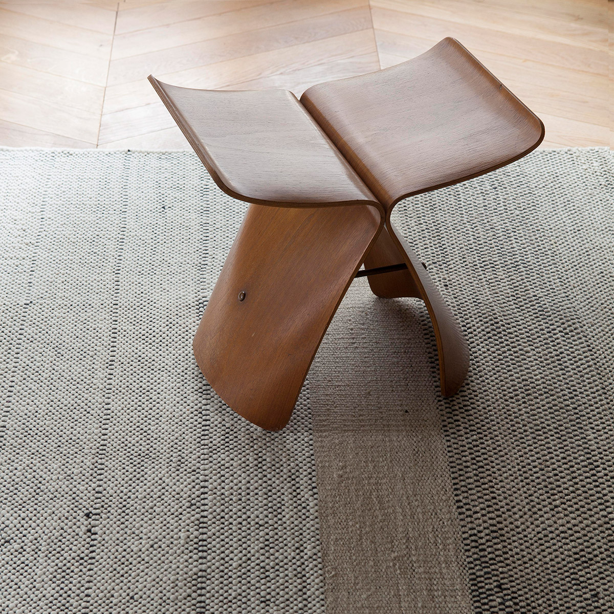 neutral textural rug with Japanese wooden stool