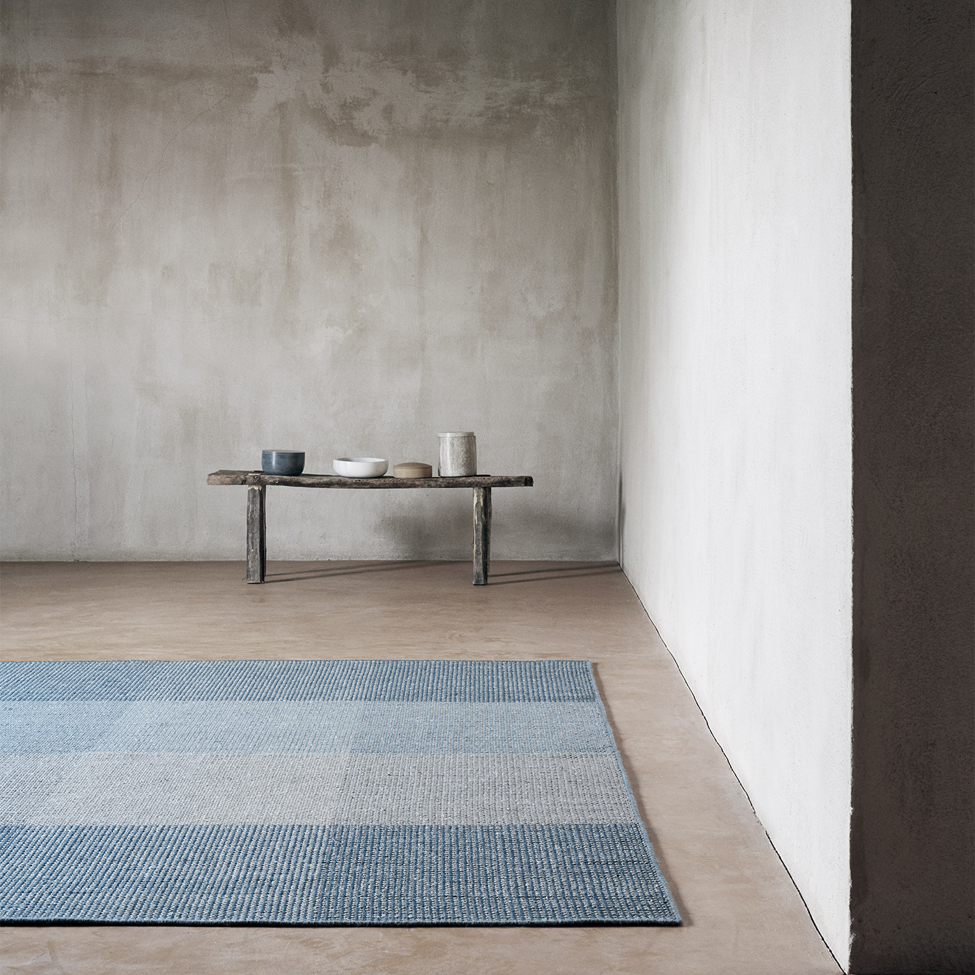 large blue grey geometric rug on concrete floor